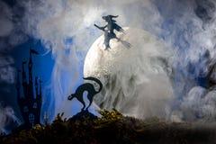 Halloween, strega su un manico di scopa nei precedenti della luna Immagini Stock