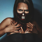 Halloween style photo of woman with fac and body art. In studio royalty free stock image