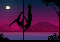 Halloween style silhouettes of male and female pole dancer performing duo tricks in front of river and full moon at night. Stock Photo
