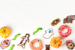 Halloween sweet treats, party food concept. Scary cookies, monster biscuits and fruits on white background. royalty free stock image
