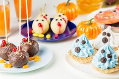 Halloween sweet treats, party food concept. White and blue cupcakes with faces close up. stock image