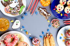 Halloween sweet treats, party food concept. Scary cookies, monster biscuits and fruits on grey background. stock photos