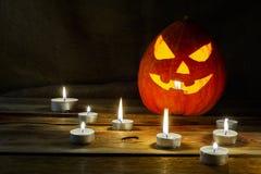 Halloween symbol smiling pumpkin lantern and burning candles royalty free stock photo
