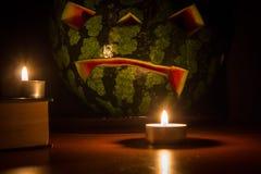 Halloween-Symbol, Wassermelone mit geschnitztem rotem lächelndem Gesicht Brennende Kerzen und Bücher auf Holztisch, dunkler Hinte Stockbilder