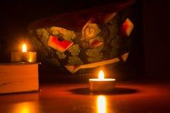 Halloween-Symbol, Wassermelone mit geschnitztem rotem lächelndem Gesicht Brennende Kerzen und Bücher auf Holztisch, dunkler Hinte Lizenzfreies Stockfoto