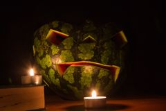 Halloween symbol, water-melon with carved red smiling face and burning candles. On dark background. Funny, handmade helloween celebrating concept. Yellow toned Royalty Free Stock Photo