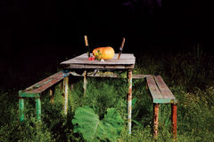 Halloween Table. A table with a pumpkin, candle and knives royalty free stock photography