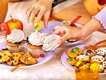 Halloween table with trick or treat and child hands. Royalty Free Stock Image