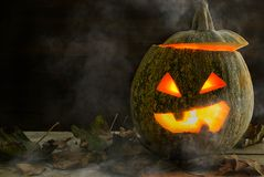 A terrible pumpkin for a holiday of Halloween in a low key. Halloween is a terrible pumpkin in the smoke with yellowed dry leaves closeup with a place for the Royalty Free Stock Photography