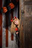 Halloween-Teufelmädchen, das aus Tür heraus schaut Lizenzfreie Stockfotos