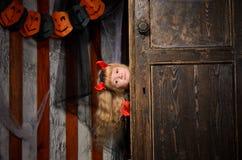 Halloween-Teufelmädchen, das aus Tür heraus schaut Lizenzfreies Stockbild