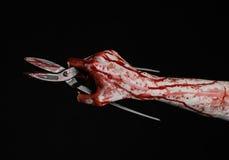 Halloween-Thema: blutige Hand, halten große alte blutige Scheren auf einem schwarzen Hintergrund Stockfotografie