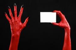 Halloween-Thema: Hand des roten Teufels mit den schwarzen Nägeln, die eine leere weiße Karte auf einem schwarzen Hintergrund halt Lizenzfreies Stockfoto
