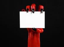 Halloween-Thema: Hand des roten Teufels mit den schwarzen Nägeln, die eine leere weiße Karte auf einem schwarzen Hintergrund halt Lizenzfreies Stockbild