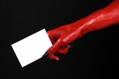 Halloween-Thema: Hand des roten Teufels mit den schwarzen Nägeln, die eine leere weiße Karte auf einem schwarzen Hintergrund halt Stockbild