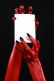 Halloween-Thema: Hand des roten Teufels mit den schwarzen Nägeln, die eine leere weiße Karte auf einem schwarzen Hintergrund halt Lizenzfreie Stockfotografie