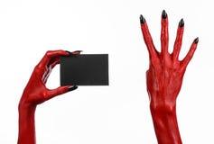 Halloween-thema: Rode duivelshand met zwarte spijkers die een lege zwarte kaart op een witte achtergrond houden royalty-vrije stock fotografie
