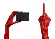 Halloween-thema: Rode duivelshand met zwarte spijkers die een lege zwarte kaart op een witte achtergrond houden Stock Foto