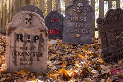Decorated cemetery with tombstones, zombies and skeletal remains. stock photos