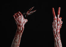 Halloween theme: bloody hand holding a big old bloody scissors on a black background Royalty Free Stock Photography