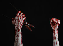 Halloween theme: bloody hand holding a big old bloody scissors on a black background Stock Image
