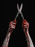 Halloween theme: bloody hand holding a big old bloody scissors on a black background Stock Images