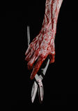 Halloween theme: bloody hand holding a big old bloody scissors on a black background Royalty Free Stock Photos