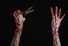 Halloween theme: bloody hand holding a big old bloody scissors on a black background Royalty Free Stock Image