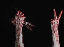 Halloween theme: bloody hand holding a big old bloody scissors on a black background Stock Photos
