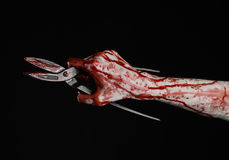 Halloween theme: bloody hand holding a big old bloody scissors on a black background Stock Photography