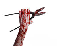 Halloween theme: bloody hand holding a big old bloody scissors on a white background Royalty Free Stock Images