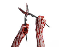 Halloween theme: bloody hand holding a big old bloody scissors on a white background Stock Photos