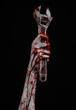 Halloween theme: bloody hand holding a big wrench on a black background Royalty Free Stock Image