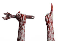 Halloween theme: bloody hand holding a big wrench on a white background Royalty Free Stock Images