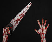 Halloween theme: bloody hand holding a bloody saw on a black background Royalty Free Stock Photos