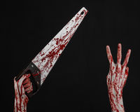 Halloween theme: bloody hand holding a bloody saw on a black background Royalty Free Stock Images