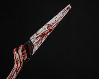 Halloween theme: bloody hand holding a bloody saw on a black background Stock Photos