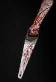Halloween theme: bloody hand holding a bloody saw on a black background Stock Image