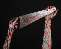 Halloween theme: bloody hand holding a bloody saw on a black background Royalty Free Stock Photo