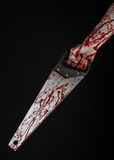 Halloween theme: bloody hand holding a bloody saw on a black background Royalty Free Stock Photography