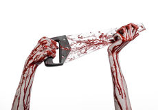 Halloween theme: bloody hand holding a bloody saw on a white background Royalty Free Stock Images
