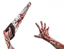 Halloween theme: bloody hand holding a bloody saw on a white background Royalty Free Stock Photography
