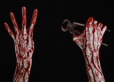 Halloween theme: bloody hand holding a pliers on a black background Stock Image