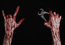 Halloween theme: bloody hand holding a pliers on a black background Stock Images