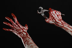 Halloween theme: bloody hand holding a pliers on a black background Royalty Free Stock Photos