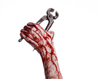 Halloween theme: bloody hand holding a pliers on a white background Royalty Free Stock Image