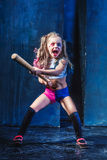 Halloween theme: Girl with baseball bat ready to hit. On dark background Stock Images
