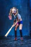Halloween theme: Girl with baseball bat ready to hit. On dark background Stock Photo