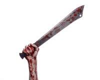 Halloween theme: hand holding a bloody machete on a white background. Studio Stock Photo