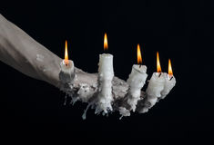 Halloween theme: on the hand wearing a candle and dripping melted wax on black isolated background Stock Image